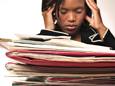 Person with head in hands behind piles of work in intray
